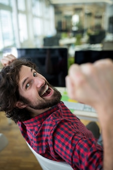 Male graphic designer cheering in office