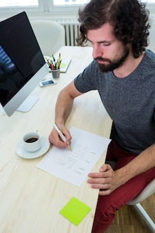 Male graphic designer filling a form
