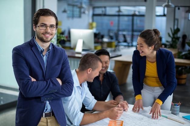 Мужской графический дизайнер, улыбаясь во время коллеги взаимодействуют над планом