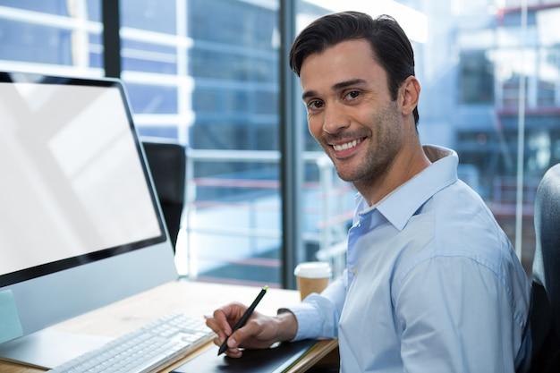 데스크에서 그래픽 태블릿을 사용하는 남성 그래픽 디자이너