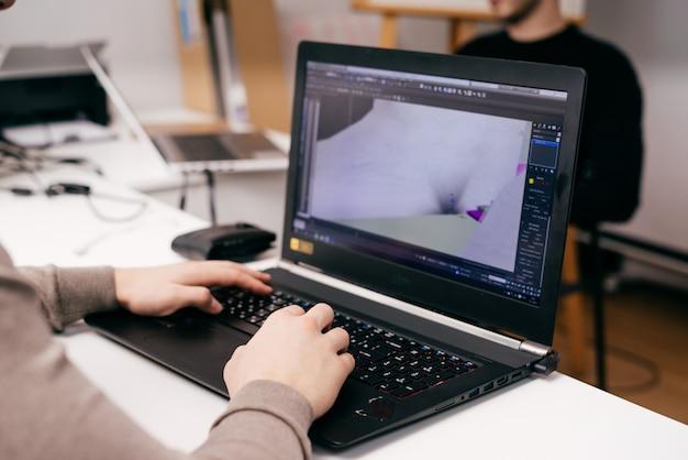 プロジェクト、事務作業でラップトップに取り組んでいる男性のグラフィックデザイナー