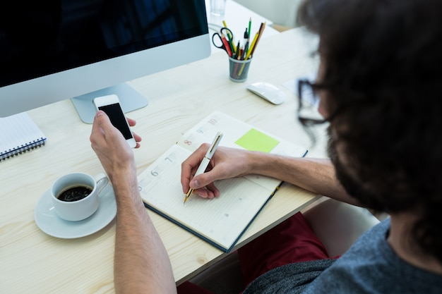 Male graphic designer writing on a diary and holding mobile phone