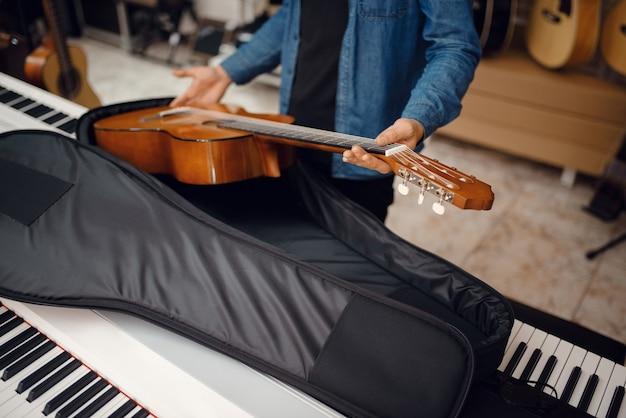 남성 기타리스트는 뮤직 스토어의 케이스에 어쿠스틱 기타를 넣습니다. 악기 상점의 구색, 음악가 구매 장비