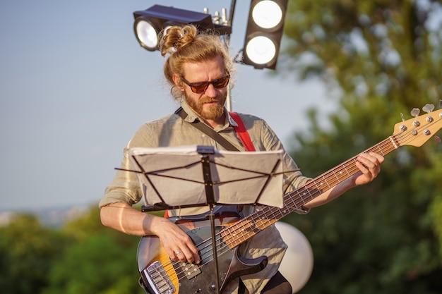 Гитарист-мужчина стоит возле пюпитра с нотами и играет мелодию на электрогитаре во время концерта на улице
