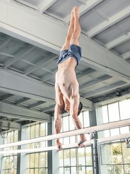Ginnasta maschio eseguendo verticale su barre parallele