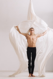 Male gymnast posing with aerial silk ribbons