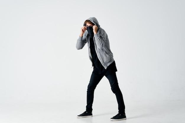 Мужчина-хакер в сером свитере ворует черную маску на лице
