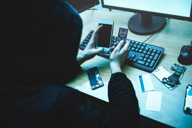 Male hacker is trying to access the phone. security and protection of personal data. the concept of cyber crime and hacking electronic devices