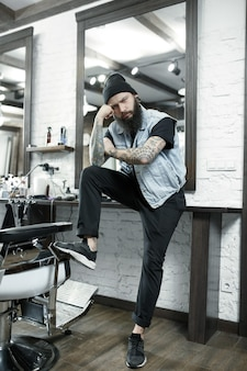 The male hairdresser against a barber shop background. the hand of the master have tattoo with the word shave