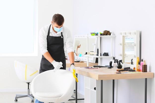 Мужской парикмахер убирает рабочее место в салоне во время эпидемии коронавируса