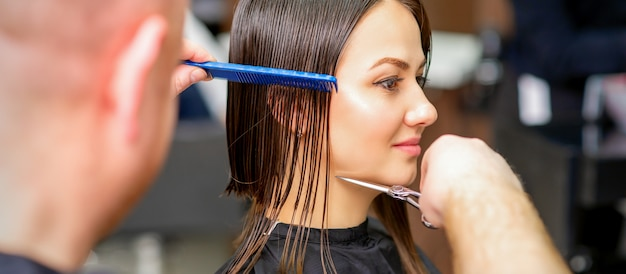 남성 미용사는 헤어 살롱에서 빗으로 빗질하는 젊은 백인 여자의 젖은 머리카락을 잘라냅니다.