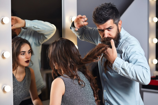 Male hairdresser cutting hair, does a hairstyle of girl client
