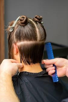美容院で櫛を持っている若い女性の髪を切る男性美容師。背面図