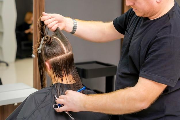 Парикмахер-мужчина держит и разделяет длинные волосы молодой брюнетки в парикмахерской