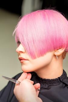 남성 미용사는 미용실에서 젊은 백인 여성을 위해 짧은 분홍색 헤어 스타일을 만듭니다.