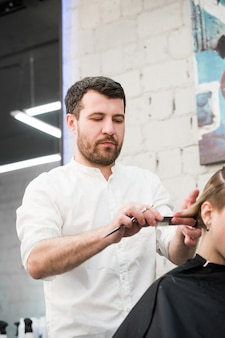 Male hairdresser making haircut for a client in professional hairdressing salon