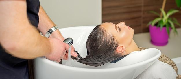 남성 미용사는 헤어 살롱에서 샴푸 후 젊은 여성의 머리카락을 헹구고 있습니다.