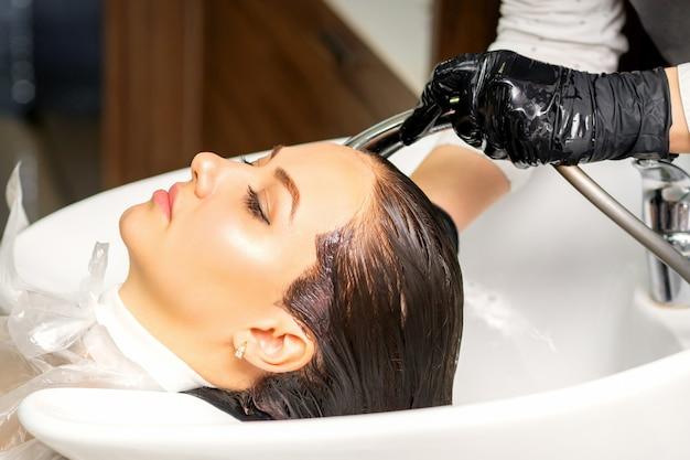 미용실에서 헤어 스타일을 만들기 전에 여성 고객에게 싱크대에서 머리카락을 씻는 남성 미용사