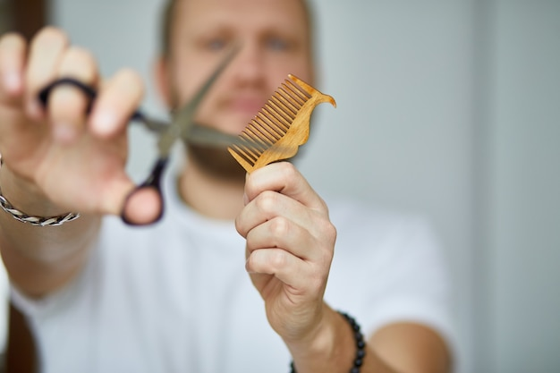 A male hairdresser wih beard, holds scissors and a comb in his hands