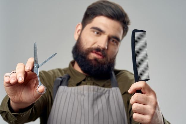 櫛はさみ灰色のエプロンひげ理髪店モデルと男性の美容師。高品質の写真