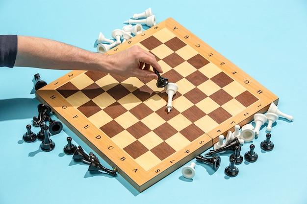 男性の手とチェス盤、ゲームのコンセプト。