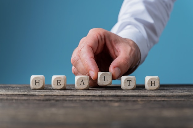 木製の立方体に綴られた健康サインを組み立てる男性の手。