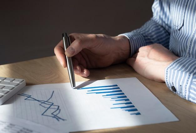 Мужская рука на столе с финансовым документом с графиком растущей тенденции. концепция экономического роста, увеличения доходов и успеха в бизнесе.