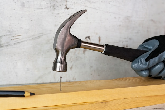 Male hand in a black construction glove hammering a nail with a hammer against the background of a concrete wall.