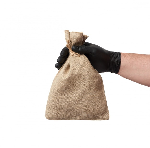 Male hand in black latex glove holds a full canvas bag on a white