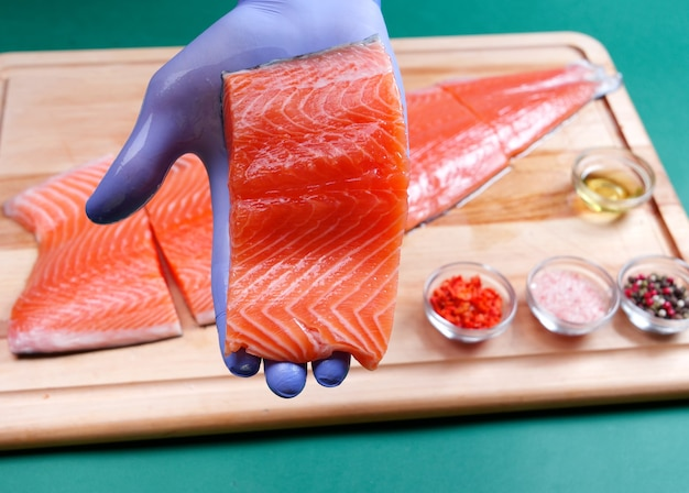 Male hand in blue gloves holds a fresh piece of raw salmon fillet, and in the background salmon and spices on a wooden cutting board