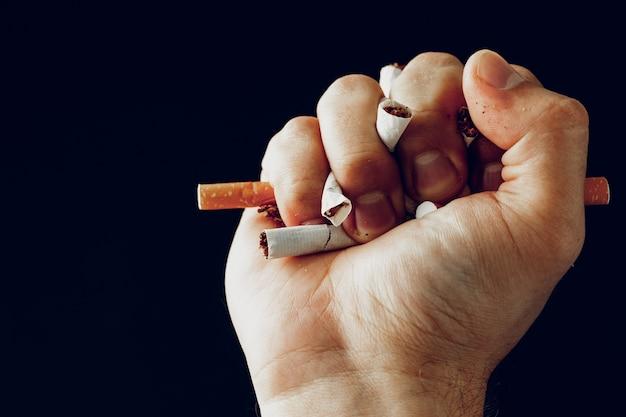 남성 손 깨는 담배를 닫습니다.