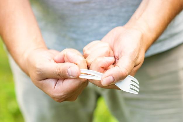 Мужская рука ломает пластиковую одноразовую вилку в парке. концепция экологических проблем. без пластика