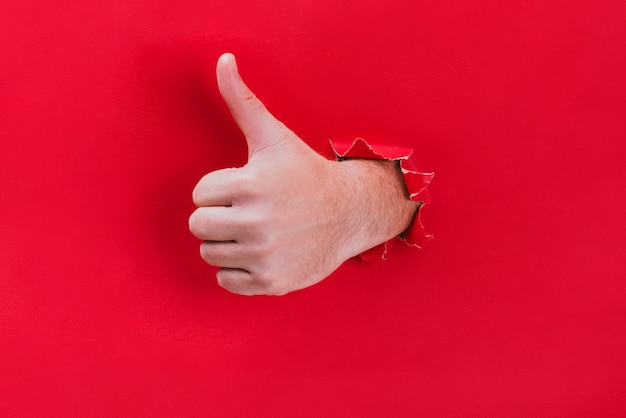 Male hand breaks through the red paper and shows his thumb up.