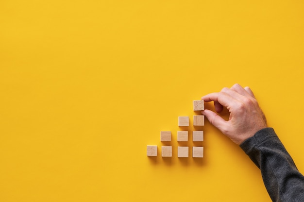 Male hand building stairway like structure with wooden blocks in a conceptual image.