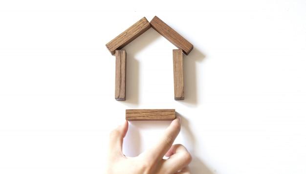 男性の手は木製のブロックから木造住宅のモデルを構築します