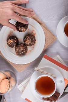 Male hand catching chocolate pastries from table. book, cup of tea, top view