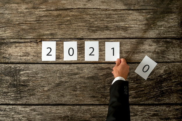 Мужская рука меняет знак 2020 на 2021 год в сборе с белыми карточками