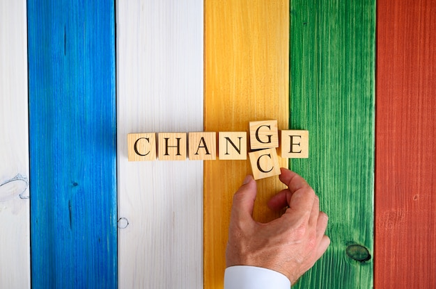 Male hand changing the word change in to chance by switching letters g and c