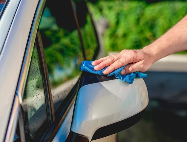 男性の手がぼろで車のミラーを洗浄