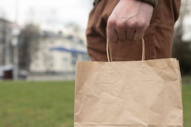Крупный план мужской руки, держащий органический коричневый пакет корабля в руке на фоне города и травы. эко образ жизни.