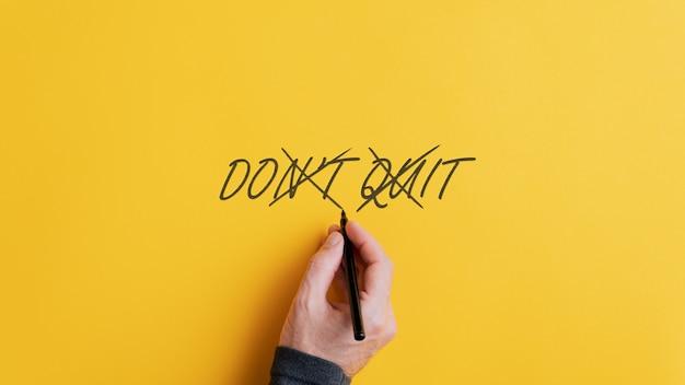 Мужская рука вычеркивает знак «не выходи», чтобы превратить его в сообщение «сделай это»