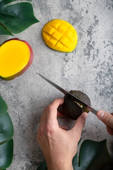 Male hand cuts fresh ripe avocado with knife on stone background.