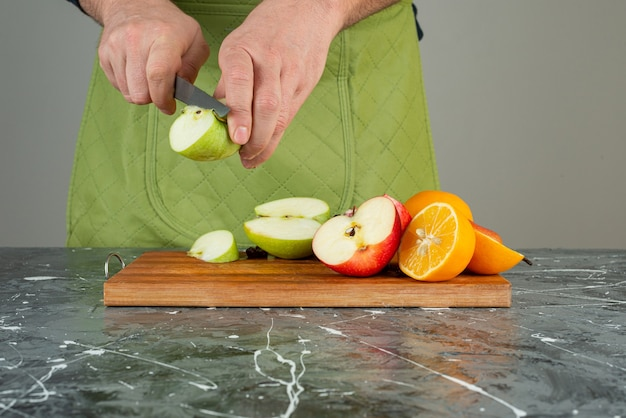 Мужская рука резки свежего яблока на деревянной доске на столе.