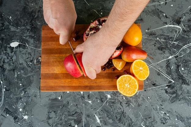 大理石のテーブルで新鮮な赤いリンゴを切る男性の手。