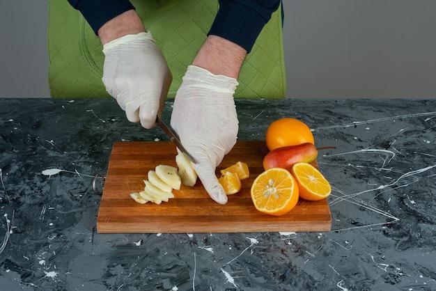 大理石のテーブルで青リンゴを手で切る男性。