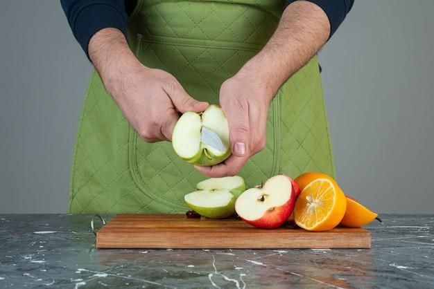Mano maschio che taglia mela verde sulla parte superiore della tavola di legno sul tavolo.