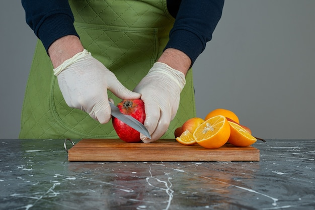 Mano maschio che taglia mela rossa in cima alla tavola di legno sul tavolo.