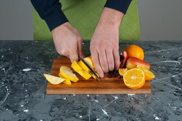テーブルの上の木の板の上に熟したマルメロを切る男性の手。