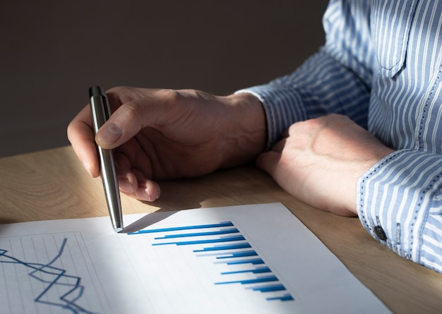 Male hand at desk with financial document with graph of growing trend. concept of economic growth, income increase and business success.