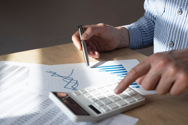 Male hand at desk with financial document with graph of growing trend, making calculations, preparing report. concept of economic growth.